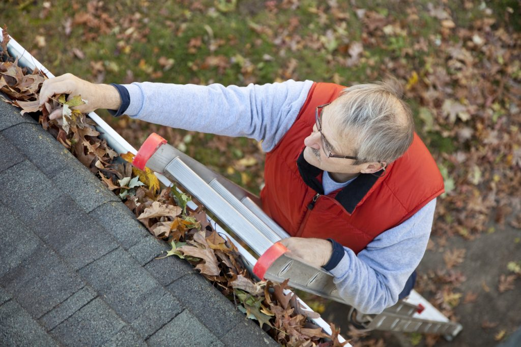 Man up ladder cleaning leafs out of gutter on house