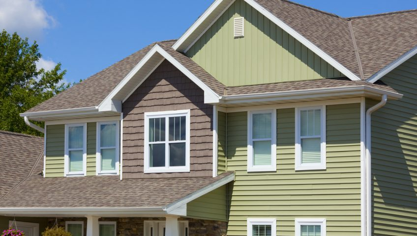 Green and Brown House of Stone, Cedar, Vinyl Siding