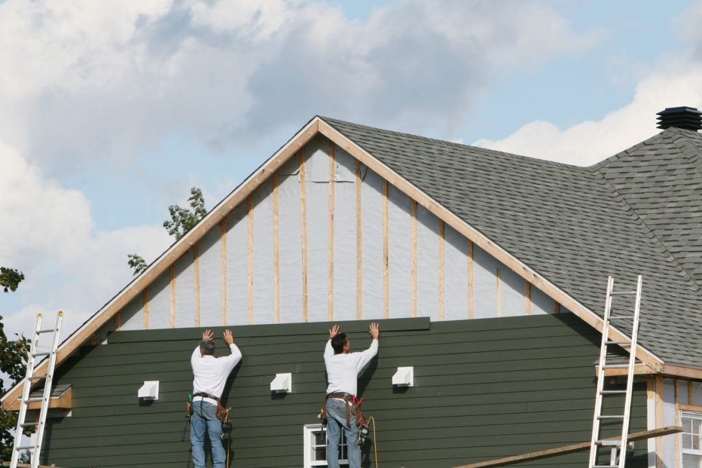 Two men applying green paneling to a house